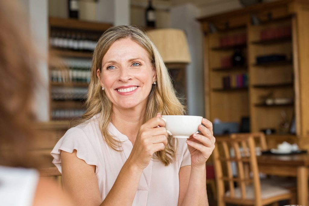 Mature woman holding coffee cup and talking with her friend.