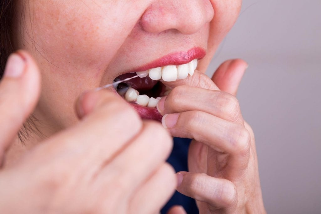 Closeup of Asian woman flossing teeth with oral floss