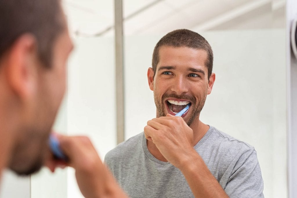 Happy man brushing teeth
