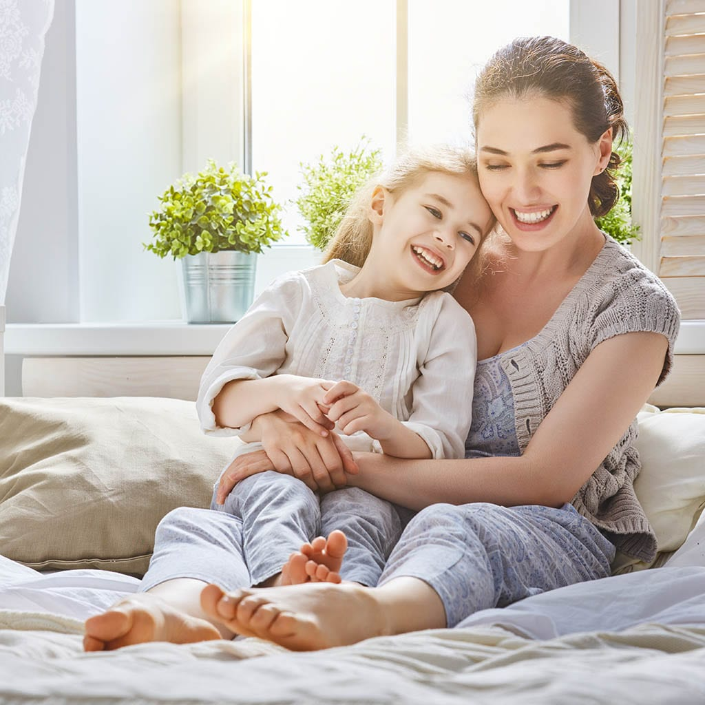 Mom and her daughter smiling while playing