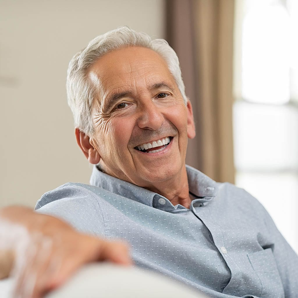 Senior man seated on couch smiling at home