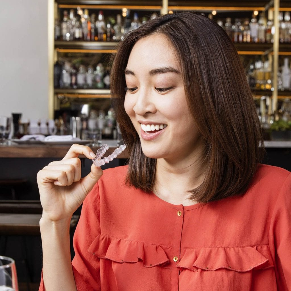 smiling woman removing her clear aligner in restaurant
