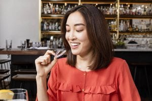 woman removing clear aligner at restaurant