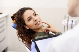 young woman sitting in dentists chair and pointing at tooth